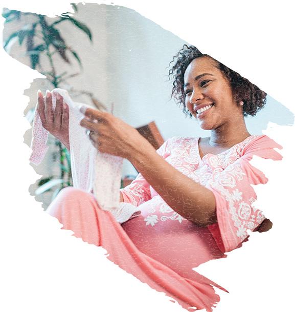 Pregnant woman admiring baby clothing.