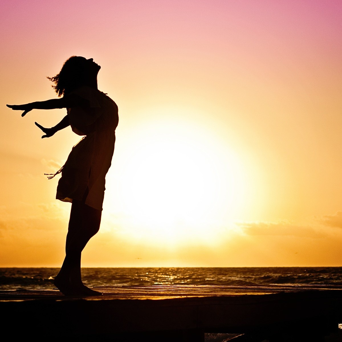 Woman on a beach during sunset with her arms outstretched
