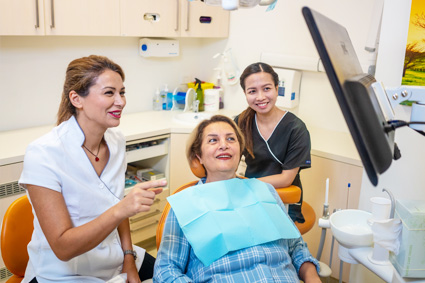 Dr and dental assistant conversing with patient