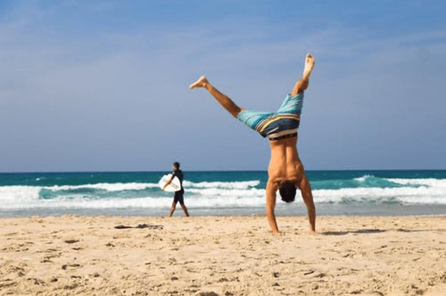 man on beach doing cartwheel