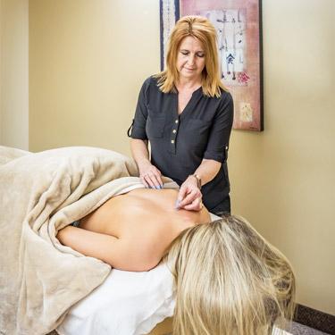 Valerie placing needles on patient