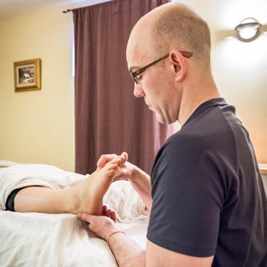 chiropractor doing reflexology on patients foot