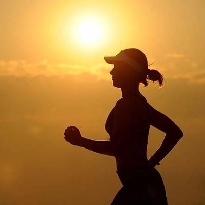 woman running on sunset backdrop