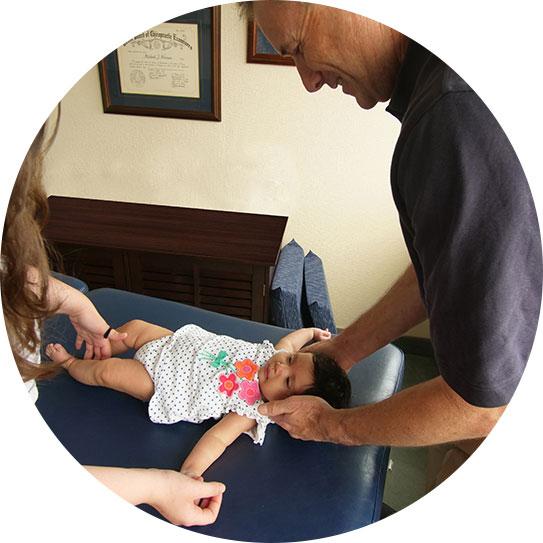 Dr. Norman adjusting baby