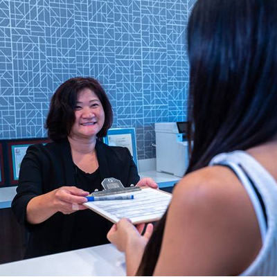 receptionist-giving-patient-paperwork
