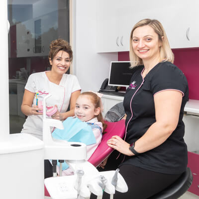 Dr Rachna with assistant and little girl in dentist chair