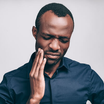 Man in blue shirt with jaw pain