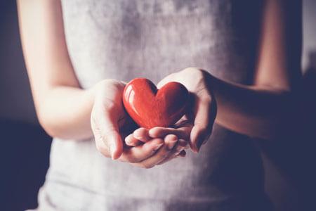 female hands holding little red heart ornament