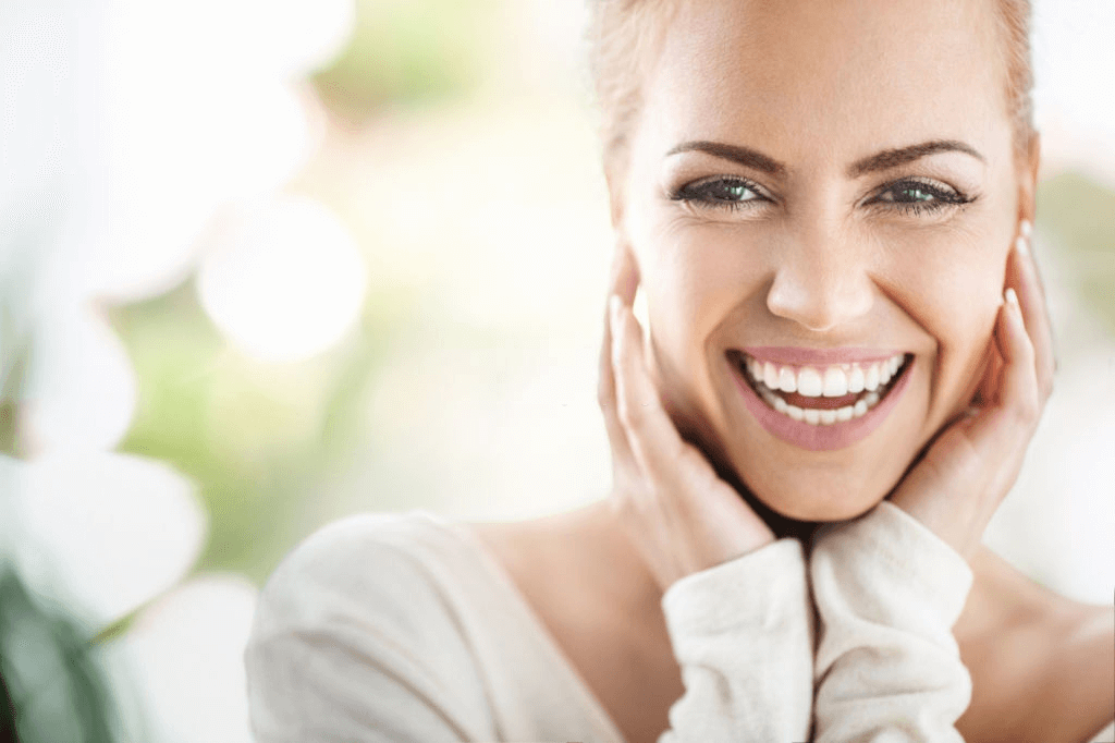woman smiling with her hands on her face