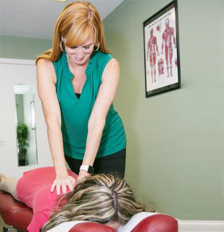 Dr Jenifer DeWald Leber adjusting a patient's upper back
