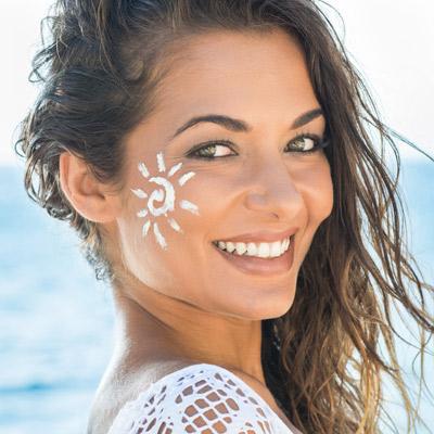 woman with sunscreen sun on cheek