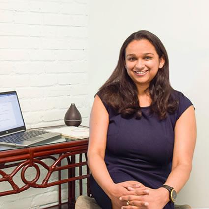 Chaitali sitting beside a desk