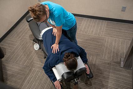 Doctor adjusting woman on table