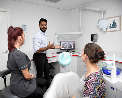 Dentist pointing to xray with patient