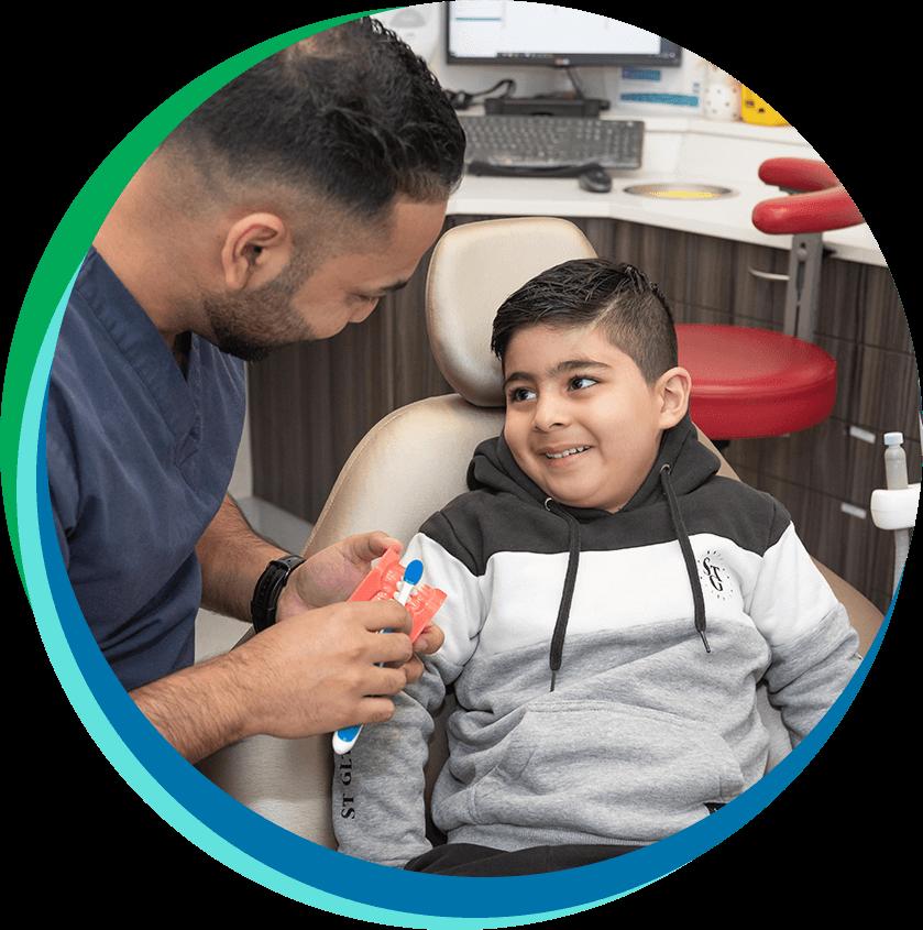 Dentist talking to boy in dental chair