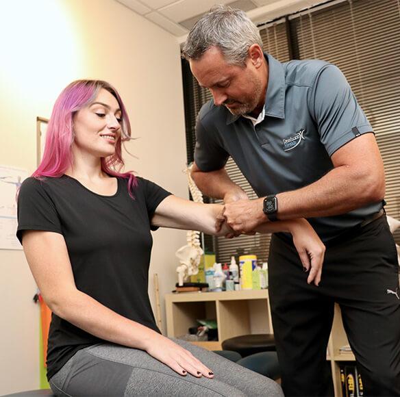Chiropractor adjusting womans arm