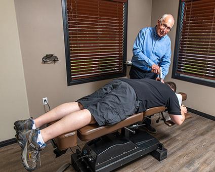 Doctor adjusting man on table