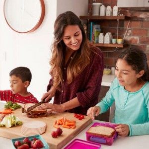 happy mom helping her two kids pack lunches