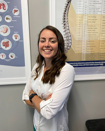 Dr. Erin standing by wall charts