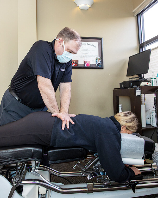 doctor pushing on woman's back