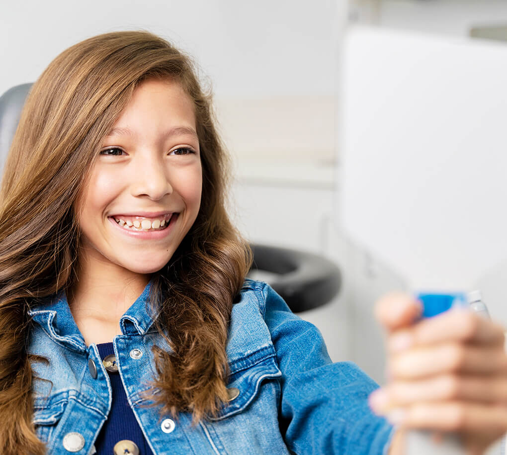 child smiling while in dental chair