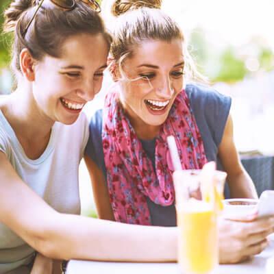 women eating laughing at phone