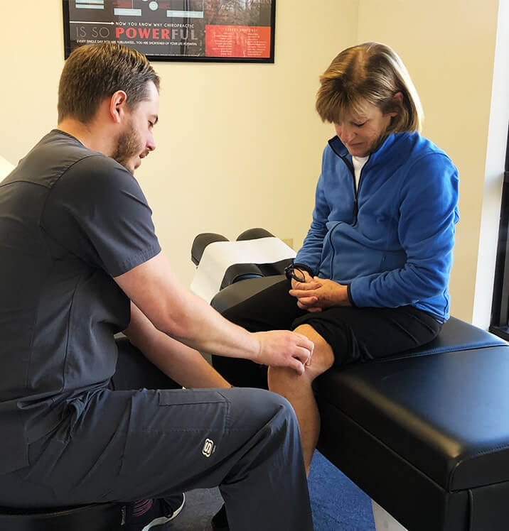 Dr. Spencer looking at patient's knee