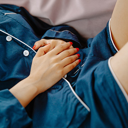 woman laying in bed with hands on stomach in discomfort