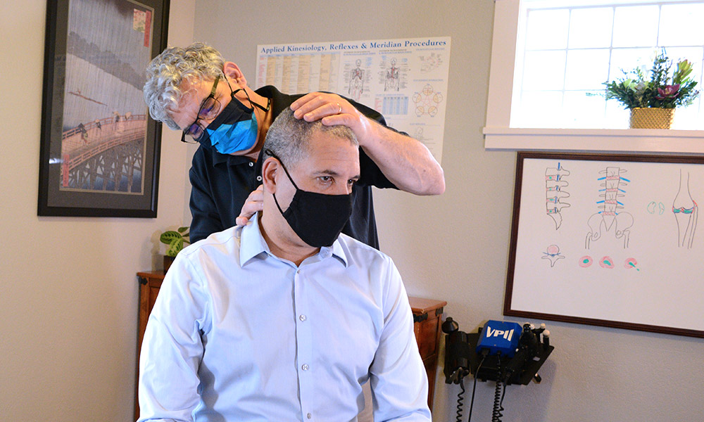 Dr. Keeler with hands on male patient neck