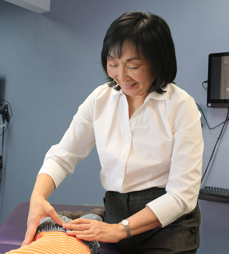 Dr. Siow's hands on toddlers back