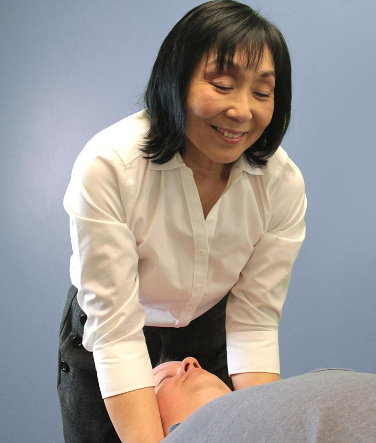 Dr. Siow adjusting patients neck