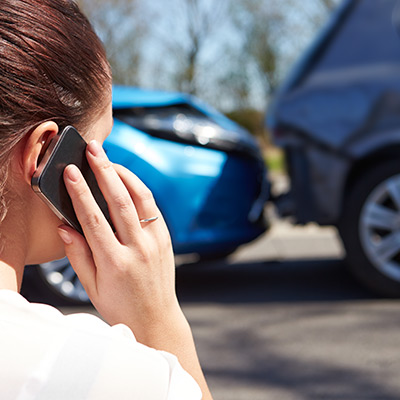 Woman talking on her cellphone after a car accident