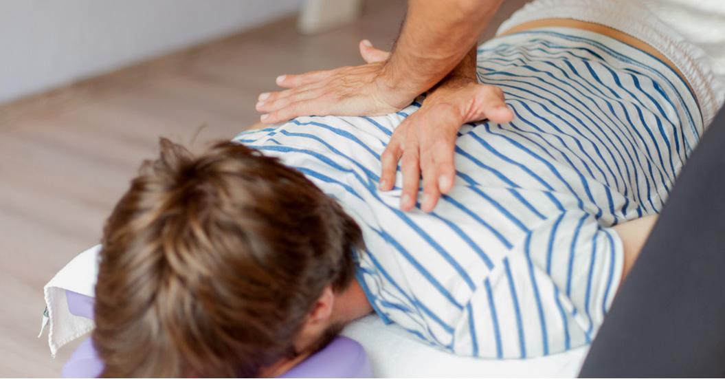 chiropractor hands adjusting patient's back