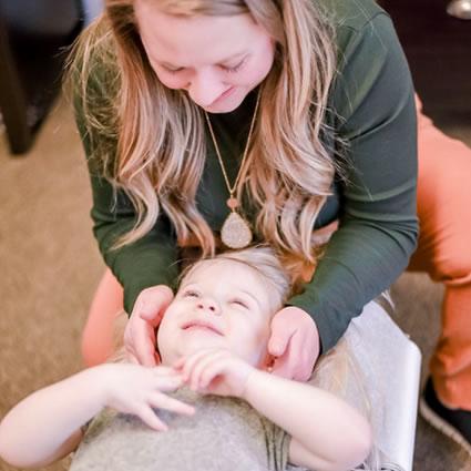Dr. Kelly adjusting little girl