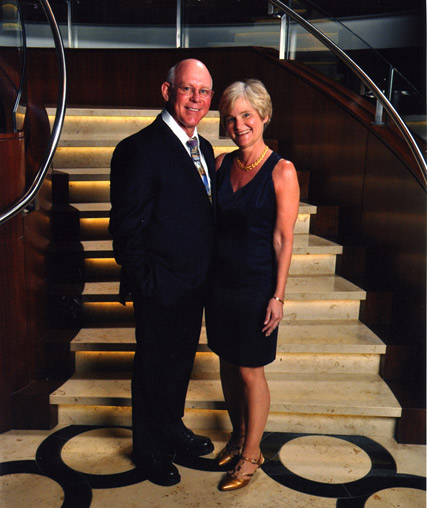 Doctor Pickens and Nancy standing at the base of the stairway in formal attire.