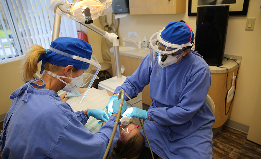 Dentists and assistant treating patient