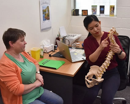Doctor pointing spine model
