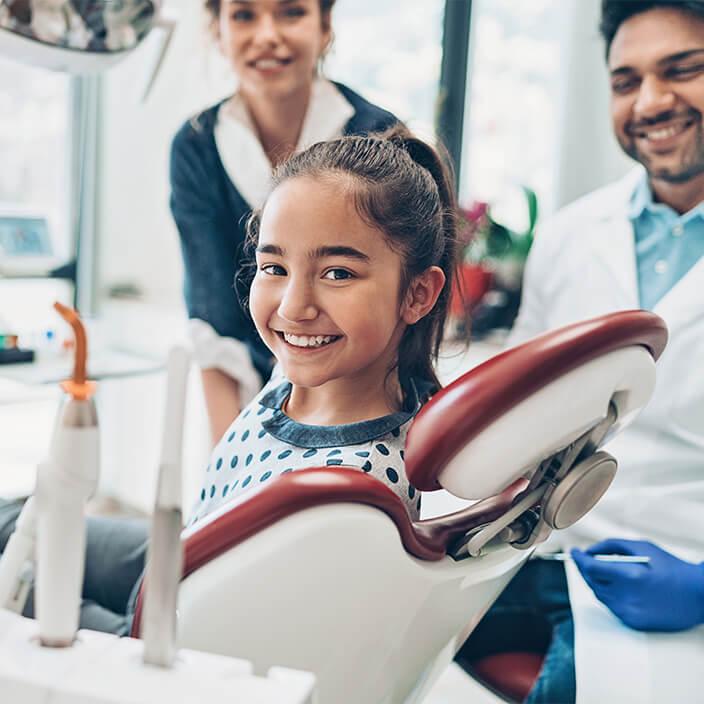 Girl in dental chair smiling