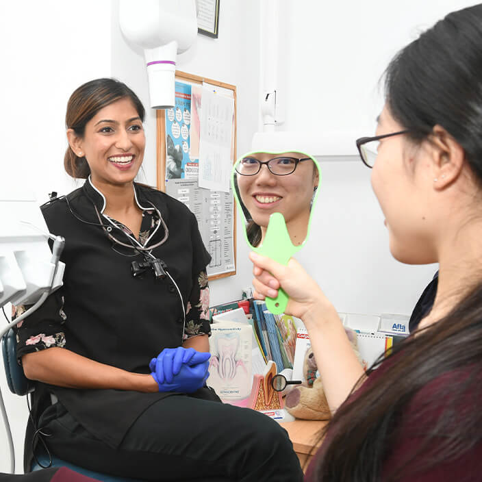 Dentist with patient looking in mirror