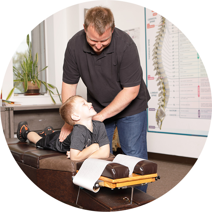 Doctor adjusting young boy on table