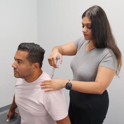 Dr. Deepa adjusting patient using activator