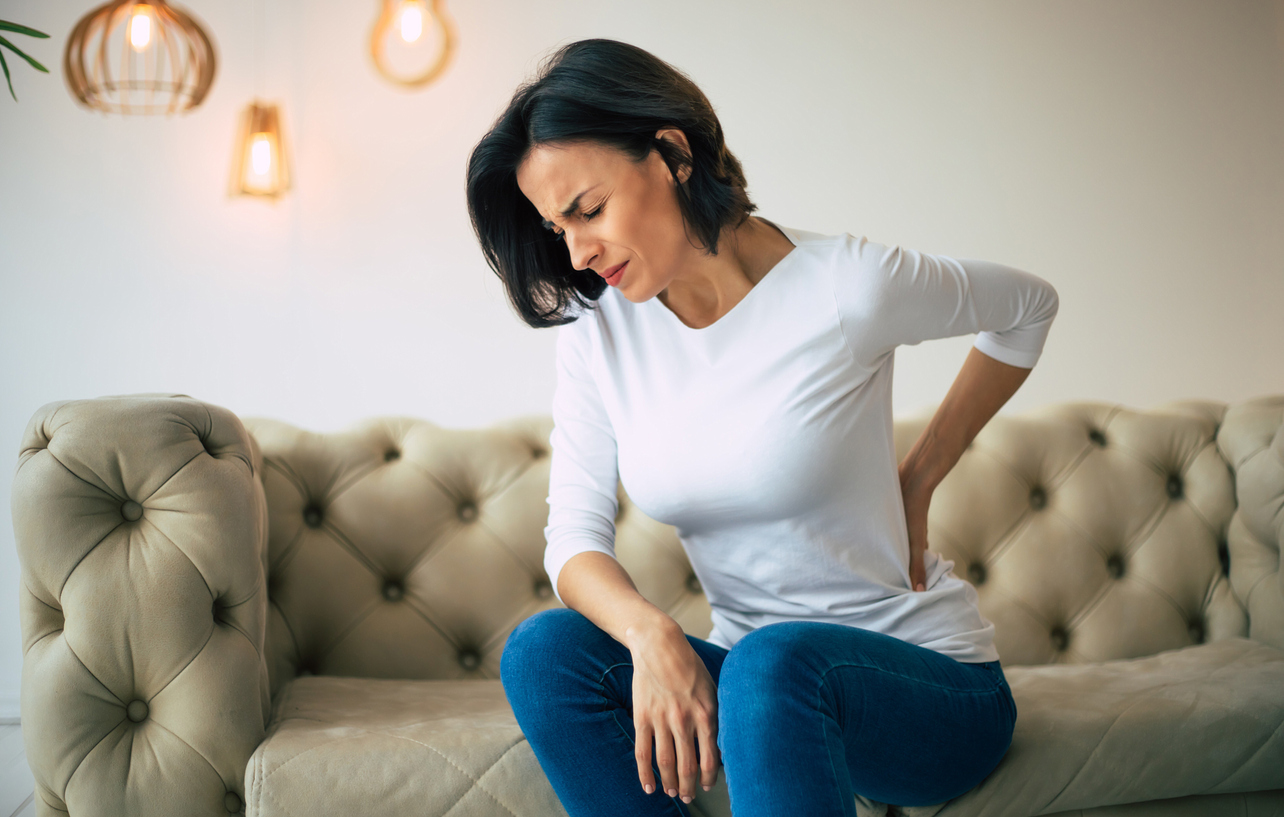Axial pain. Close-up photo of a hurting woman, who is sitting on a couch and holding her lower back with her left hand.