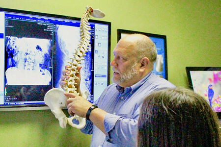 Dr. Steve Niemiec educating patient with model of spine