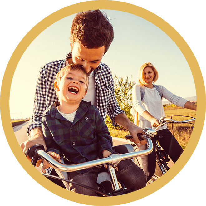 boy laughing on bike with dad