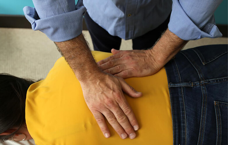 Dr Diamond with hands on patients back