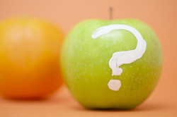 Green apple with question mark painted on it.