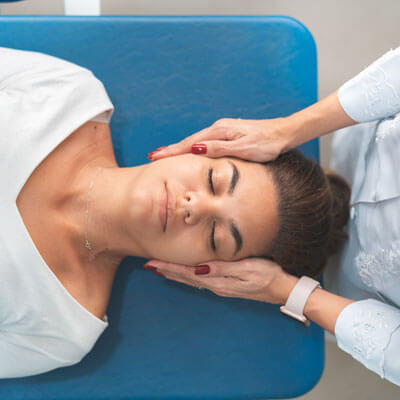 Woman getting her neck adjusted at a chiropractor