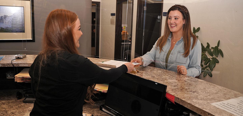 receptionist handing card to patient