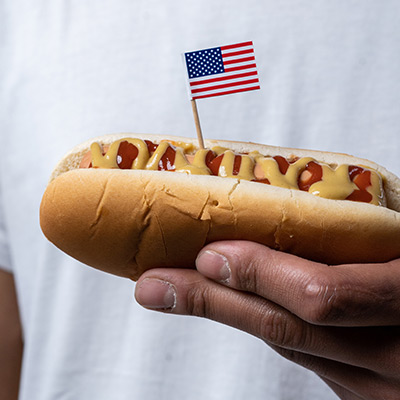 man holding a hot dog with an american flag pick stuck in it