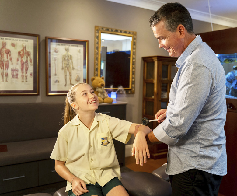 Doctor checking girls elbow